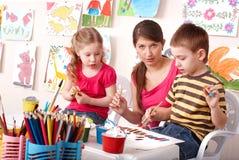 Niños que pintan con el profesor en escuela. Imagen de archivo libre de regalías