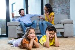 Niños que ponen en la alfombra en sala de estar Imagen de archivo libre de regalías