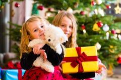 Niños que reciben presentes en la Navidad Imagen de archivo libre de regalías