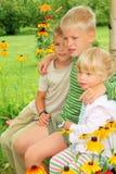Niños que se sientan en banco en jardín Fotos de archivo