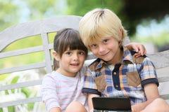 Niños que se sientan en el jardín que juega a juegos Foto de archivo libre de regalías