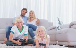 Niños que se sientan en la alfombra que juega a los videojuegos Foto de archivo libre de regalías