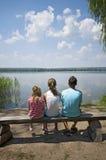 Niños que se sientan en la orilla del lago Imágenes de archivo libres de regalías