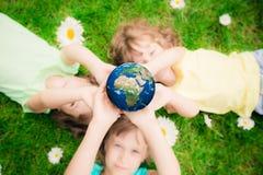 Niños que sostienen el planeta de la tierra en manos Foto de archivo libre de regalías