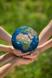 Niños que sostienen el planeta de la tierra en manos Imagen de archivo libre de regalías