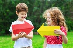 Niños que sostienen la flecha del color que señala a la derecha y a la izquierda, en verano Imágenes de archivo libres de regalías