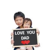 Niños que sostienen la pizarra con amor del texto usted papá Foto de archivo libre de regalías