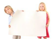 Niños que sostienen un documento en blanco de la cartulina sobre blanco Foto de archivo