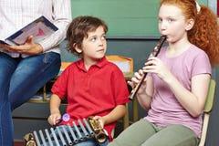 Niños que tienen lecciones de música en escuela Fotografía de archivo libre de regalías