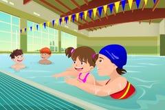 Niños que tienen una lección de la natación en piscina interior Fotos de archivo libres de regalías