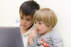 Niños que usan la computadora portátil Imágenes de archivo libres de regalías