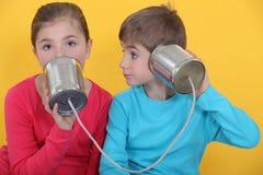 Niños que usan las latas como teléfono Imágenes de archivo libres de regalías