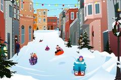 Niños Sledding en una calle Nevado durante la estación del invierno Fotografía de archivo