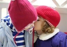 Niños, sombrero rojo del invierno susurrando en oído Imagen de archivo