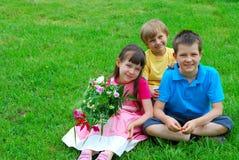 Niños sonrientes en hierba Fotografía de archivo libre de regalías