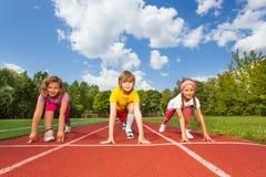 Niños sonrientes en las rodillas de doblez listas para correr Fotografía de archivo libre de regalías
