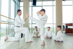 Niños éticos multi jovenes, hermosos, acertados en la posición del karate Imagen de archivo