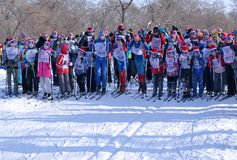 Niños y adultos al inicio de las competencias del esquí Foto de archivo libre de regalías