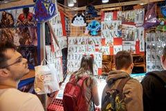 Niños y adultos que compran recuerdos y objetos diversos del culto Fotos de archivo libres de regalías