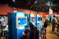 Niños y adultos que juegan las videoconsolas de WII U Imagen de archivo