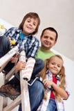 Niños y su padre listos para pintar el cuarto Fotos de archivo libres de regalías
