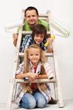 Niños y su padre que consiguen listos para pintar el cuarto Imagen de archivo