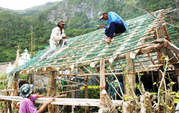 Nipa hut bayanihan construction. Picture of workers building a nipa hut through Bayanihan Stock Images