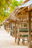 Nipa huts on the white coral sand beach surrounded with palms Royalty Free Stock Photos