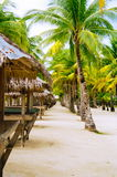 Nipa huts on the white coral sand beach surrounded with palms Stock Photo