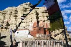 Niphu monastery, upper Mustang,. Niphu monastery in the sandstone cliff, and prayer flags. Blazing colors, red, ocher, white on blue sky. Nepal, Himalaya Royalty Free Stock Photo