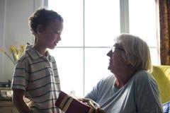 Nipote che dà un regalo a sua nonna fotografia stock libera da diritti