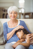 Nipote che dorme sul rivestimento delle nonne in salone Immagini Stock Libere da Diritti