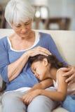 Nipote che dorme sul rivestimento delle nonne in salone Fotografie Stock