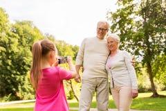 Nipote che fotografa i nonni al parco Immagini Stock