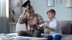 Nipote che gioca con l'aeroplano del giocattolo, nonno in cappuccio che saluta a poco pilota fotografia stock