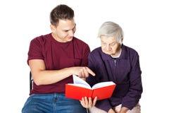 Nipote che legge un romanzo con la nonna Immagini Stock Libere da Diritti