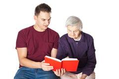 Nipote che legge un romanzo con la nonna Fotografia Stock