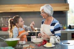Nipote che mette farina sul naso delle nonne Fotografia Stock