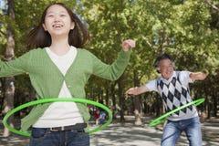 Nipote con il nonno divertendosi e giocando con il cerchio di plastica nel parco Immagine Stock