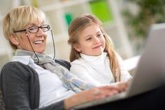 Nipote d'istruzione della nonna moderna come utilizzare computer portatile Fotografia Stock Libera da Diritti