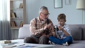 Nipote di spiegazione del nonno come usare retro macchina fotografica, giovani sogni del fotografo fotografie stock