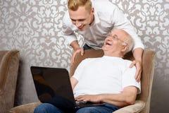 Nipote dietro suo nonno con il computer portatile immagine stock libera da diritti