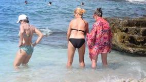 Nipote e nonna che camminano verso il mare per godere dell'acqua di mare archivi video