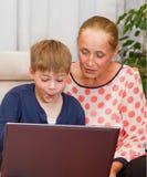 Nipote e nonna che loking al computer portatile Immagini Stock