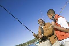 Nipote e nonno che pescano insieme Fotografia Stock