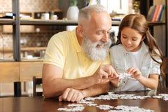 Nipote e nonno che provano ad unire due pezzi di puzzle Fotografie Stock Libere da Diritti