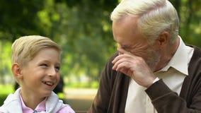 Nipote e nonno che ridono e che si divertono godendo del giorno in parco insieme video d archivio