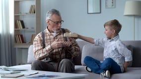Nipote preoccupantesi che dà presente al nonno, all'attenzione ed alla cura per i cari immagine stock libera da diritti