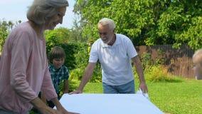 Nipoti che aiutano i nonni a mettere tavola con il panno bianco, visita di festa video d archivio