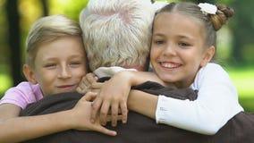 Nipoti che corrono al nonno che si siede sul banco, abbracciante lo e baciante stock footage